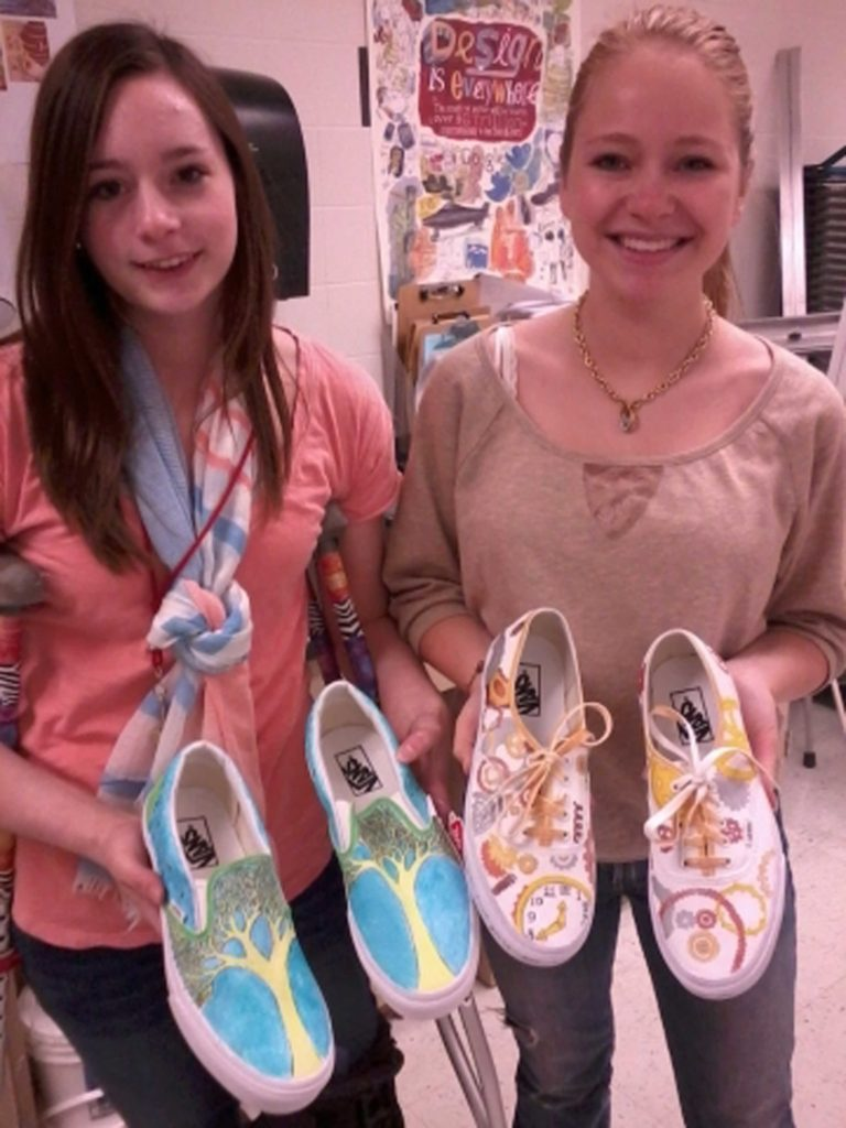 Students+Maddie+Mayhew+and+Taylor+Werdel+show+off+their+winning+shoe+designs.+Their+designs+were+sent+to+be+judged+by+the+nation.+Photo%2F+Sidney+Fairbrother